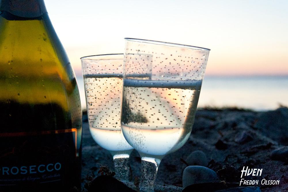 Glas med bubbel på stranden på Ven