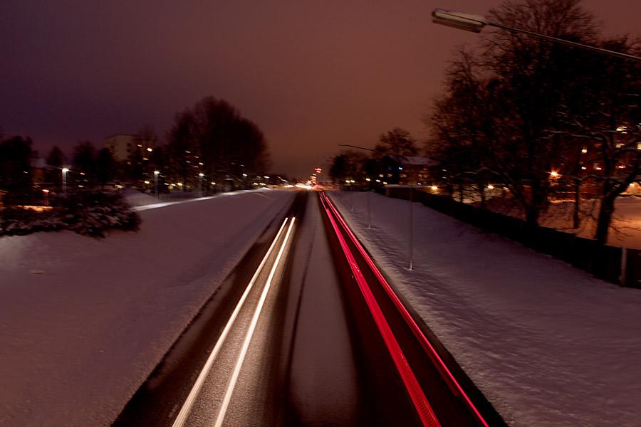 Nattfotografering av bilar på vägen